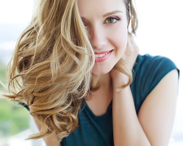 Woman with long flowing hair covering one side of her face smiling