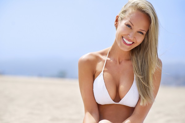Woman in a white plunge beach smiling and sitting on the beach after breast augmentation