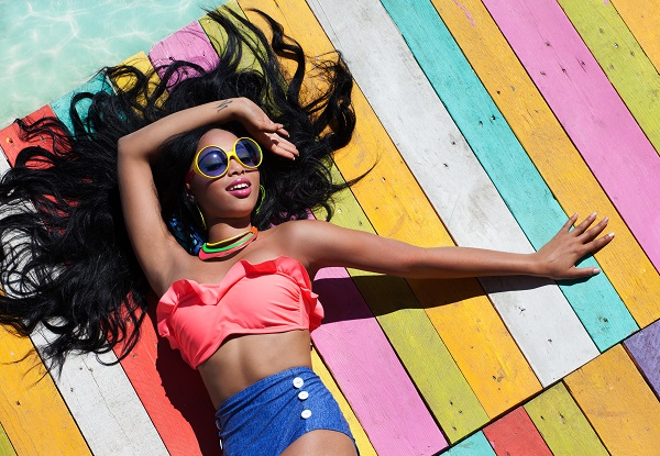 Woman with her hair spread out laying down on a boardwalk at the ocean