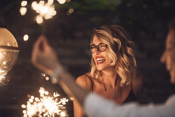 Beautiful blonde woman with style hair and glasses laughing at a holiday celebration with sparklers in the foreground